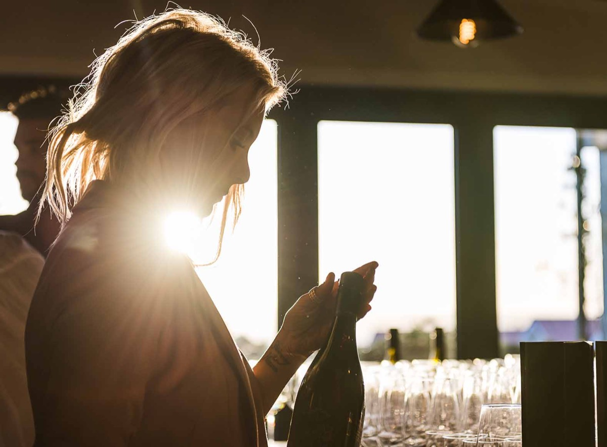 Woman opening a bottle of wine in a social setting