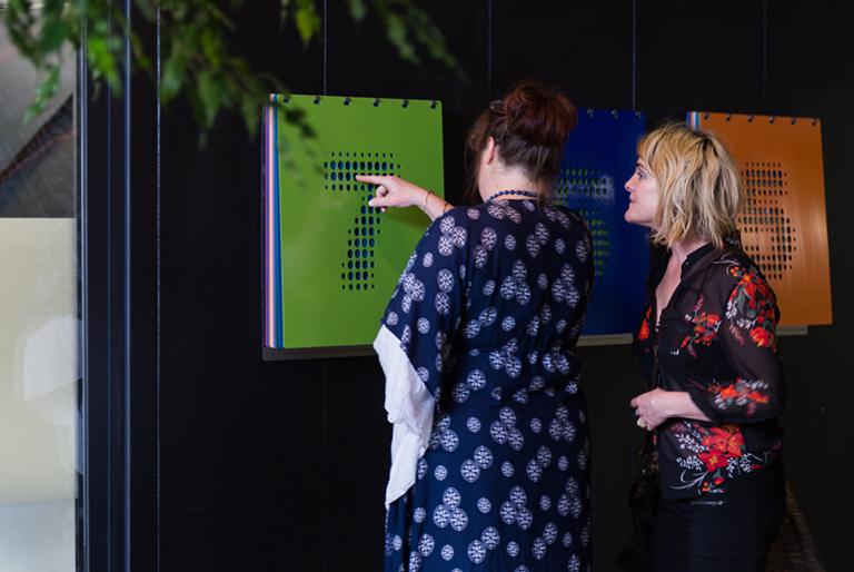 Two women discussing artwork at a Qb Studios art event