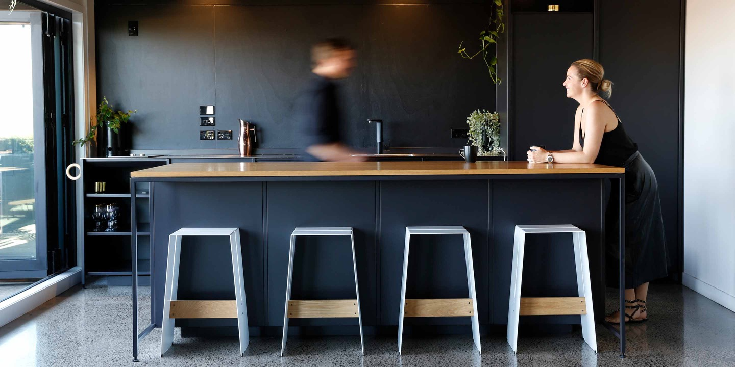 A man and woman in a shared kitchen space at Qb Studios Ponsonby