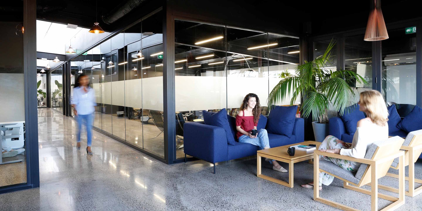 Two women relaxing in a furnished communal space at Qb Studios Ponsonby